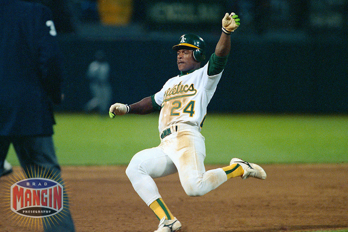 OAKLAND, CA - Rickey Henderson of the Oakland Athletics steals third base during a game at the Oakland Coliseum in Oakland, California in 1991. Photo by Brad Mangin