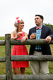 USA, Tennessee, Nashville, Iroquois Steeplechase, a young man and woman by a fence drinking Moonshine Cherry-Basil Blush and Tennessee Whiskey