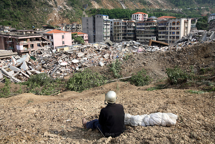 A man sits by the body of his son, a third grader, that he recovered from the ruins of a collapsed school complex in Beichuan, Sichuan, China on 15 May 2008. China now estimates the death toll to be around 50,000 as prospects of survival for those still buried diminishes.