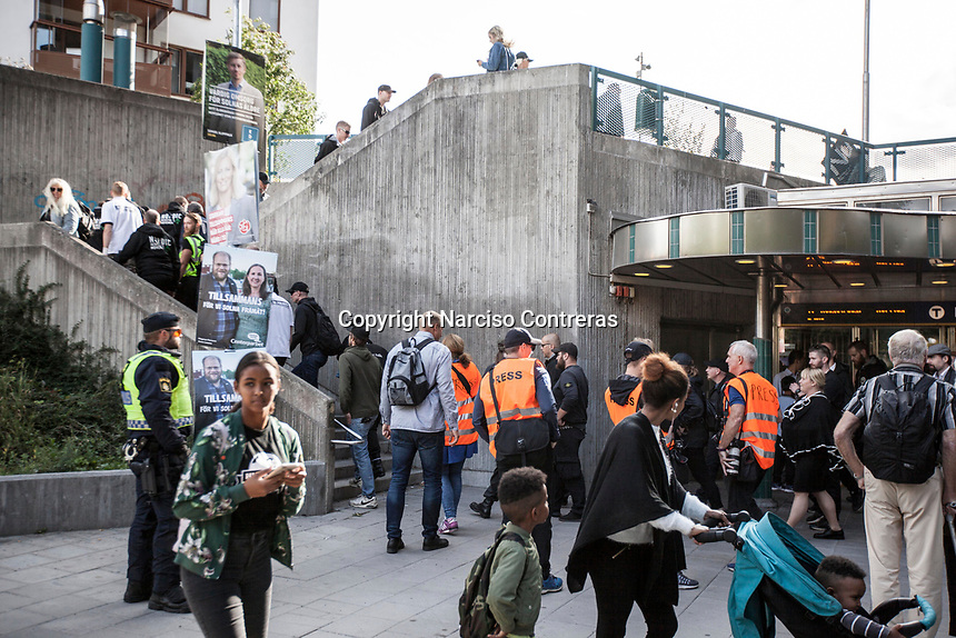 August 25, 2018: Pedestrians react as supporters of the neo Nazi Nordic Resistance Movement NRM (Nordiska motståndsrörelsen) are escorted by police forces out of a metro station after a demonstration at the Kungsholmstorg square in Stockholm, Sweden. An estimate of 200 supporters of the neo-Nazi organisation held a six-hour rally guarded by a strong police deployment.