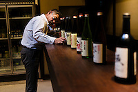"Tokubee Masuda, CEO of the Tsukinokatsura sake brewery preparing bottles of sake for tasting. Fushimi, Kyoto, Japan, October 10, 2015. Tsukinokatsura Sake Brewery was founded in 1675 and has been run by 14 generations of the Masuda family. Based in the famous sake brewing region of Fushimi, Kyoto, it has a claim to be the first sake brewery ever to produce ""nigori"" cloudy sake. It also brews and sells the oldest ""koshu"" matured sake in Japan."