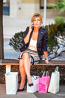 Attractive female shopper with mobile smartphone and shopping bags at an Austin outdoor shopping mall