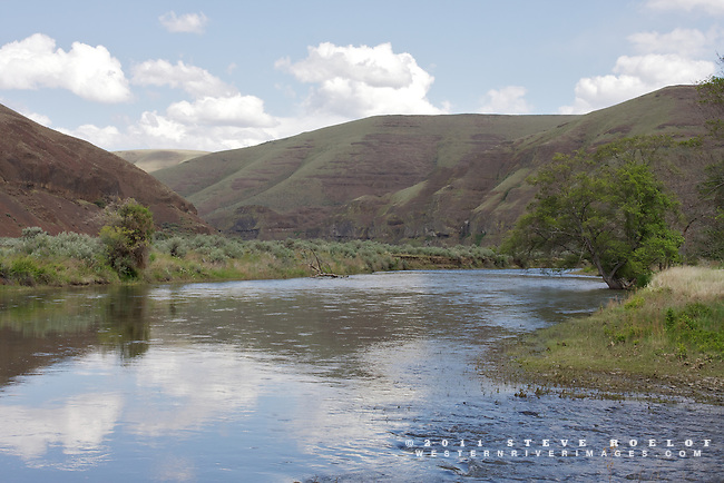 The blue sky reflects in the John Day River, Oregon.