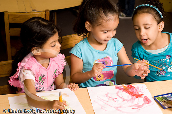 Education Preschool 4-5 year olds art activity water color painting three girls sititng and looking at one girl using brush on her own hand talking and interested horizontal