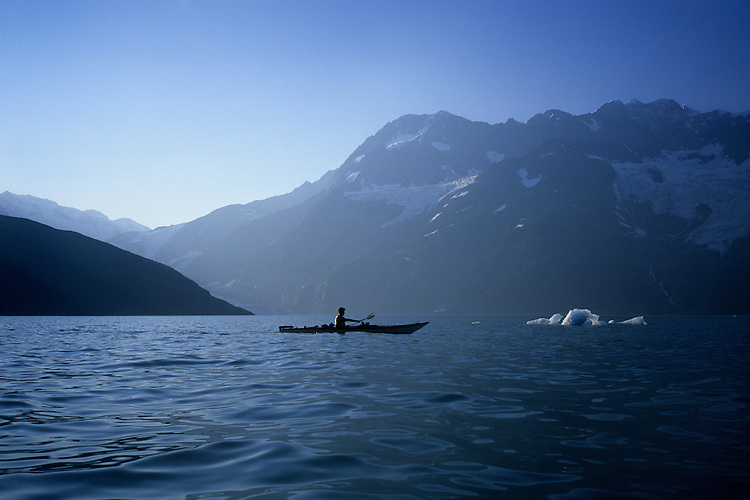 A kayaker paddles near glacial ice floating in Prince William Sound's Harriman Fjord as the sun sets behind the Chugach Mountains.