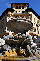 In piazza Mincio in Rome, in the heart of the quarter designed by Gino Coppedé, the typical fountain which is named Fountain of the Frogs since the water sorts from the mouths of these sculpted animals, with one of the typical buildings of the square on the background. It was a sunny day and the water was flowing. Digitally Improved Photo.