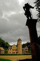 Silhoutted statue overlooking the medieval castle of Mespelbrunn. Mespelbrunn close to Aschaffenburg, Elsava valley. Germany