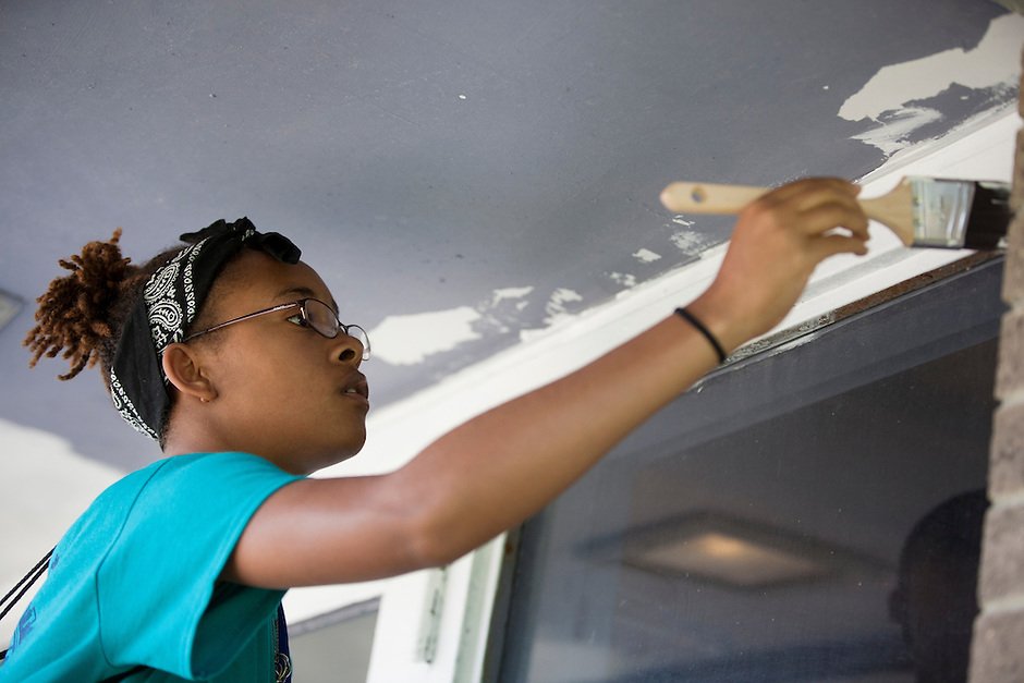 """LaVerne Handfield paints a window frame outside of an entryway during """"Circle the City with Service,"""" the Kiwanis Circle K International's 2015 Large Scale Service Project, on Wednesday, June 24, 2015, at the Friendship Westside Center for Excellence in Indianapolis. (Photo by James Brosher)"""