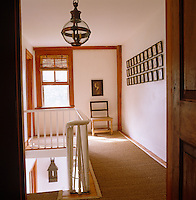 View through open doorway to the landing with a sisal runner and a series of framed prints on the wall