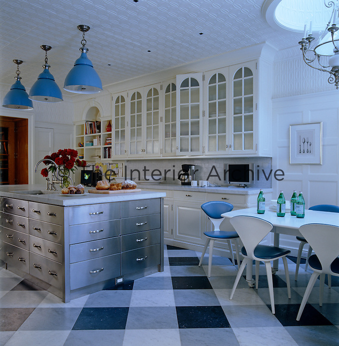 The kitchen has three large blue industrial pendant lights hanging over the stainless steel island and a gingham-patterned marble floor