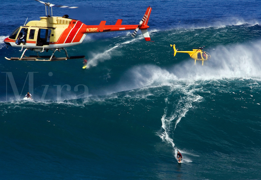 Helicopters filming tow-in surfers at Peahi (Jaws) off Maui. Hawaii.