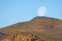 The moon rises over a mountain in the Mojave Desert, California.