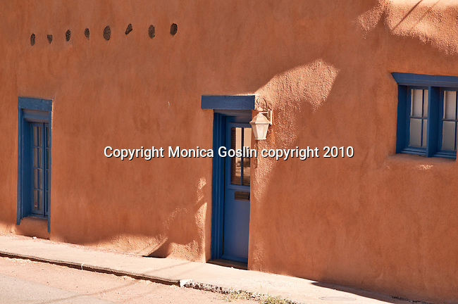 An adobe building with bright blue windows and doors on Canyon Road, an art district with over one hundred galleries and studios in Santa Fe, New Mexico