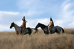 Two Native American Indian men sitting bareback on a horse in traditional Sioux Indian clothing in South Dakota