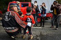 "Fire department chief with children having his photo taken. Housui Gassen (fire-hose battle), Bizen city, Okayama pref, Japan, February 2, 2014. The annual Bizen ""Housui Gassen"" (fire-hose battle) takes place in the Hinase port area. Opposing teams of fire-fighters spray each other with hoses before the event culminates with a display of coloured water from the hoses."