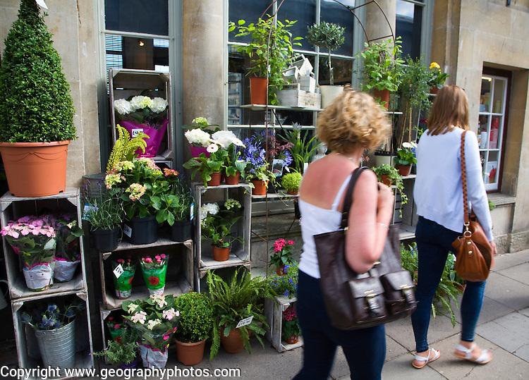 Female shoppers walking past flower shop on Pulteney Bridge, Bath, Somerset, England