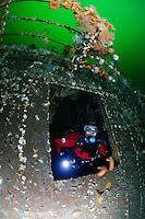 TA0340-D. Scuba diver (model released) peers out of the HMCS Chaudiere, a 366-foot long artificial reef which was once a Canadian warship. It was sunk in 1992 in Sechelt Inlet and is a popular advanced scuba dive, with depths between 60 and 140 feet. Much of the wreck is covered in giant plumose sea anemones (Metridium farcimen) and tunicates (Ciona savignyi). Here the diver, having penetrated into the interior to explore carefully prepared chambers and passageways, now exits through an opening midships. British Columbia, Canada, Pacific Ocean. <br /> Photo Copyright &copy; Brandon Cole. All rights reserved worldwide.  www.brandoncole.com