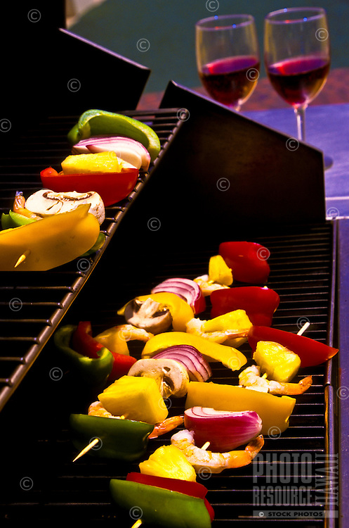 Two glasses of wine accompany shrimp kebabs with red, green and yellow peppers, pineapple, red onion and mushrooms on gas grill, poolside.