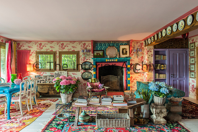 The living/dining area is a riot of pattern and colour with textiles, furniture and wallpaper all competing for attention