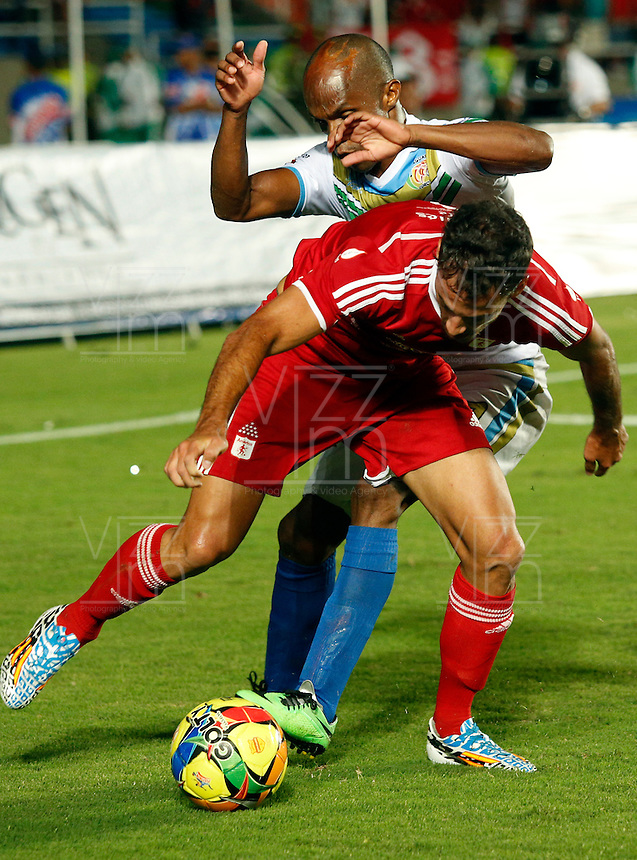 CALI - COLOMBIA - 08-06-2014: Jorge Brazales (Izq.) jugador del America disputa el balón con Luis Sánchez (Der.) jugador de jaguares FC, durante partido de vuelta entre America de Cali y Jaguares FC, de la jugado en el estadio Pascual Guerrero de la ciudad de Cali. / Jorge Brazales (L) player of America, figths for the ball with Luis Sánchez (R) player of Jaguares FC, during a match for the second leg between America de Cali and Jaguares FC, ??played at the Pascual Guerrero stadium in Cali. Photo: VizzorImage / Juan C. Quintero / Str.