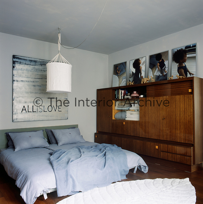 The main bedroom has a retro feel with a free-standing cupboard unit to one side. The double bed has grey blue bedding