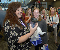NWA Democrat-Gazette/ANDY SHUPE<br /> Fayetteville High School senior Cesca Craig (center) smiles Thursday, May 10, 2018, after presenting Kelly Williams, an advanced placement calculus teacher, with a gift during an academic signing ceremony in the Matthew Moore Library at the school. Craig plans to attend New York University and study anthropology.