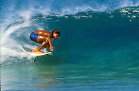 Local boy surfing on a bright blue wave at ehukai beach on Oahu's famous north shore