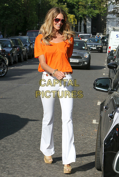 ELLE MACPHERSON .pictured in London, England, UK, .May 3rd 2011..full length jeans wide leg flares white denim orange t-shirt tee top sunglasses red aviators  belt smiling curly hair  wavy platform shoes peep toe beige cream  gold bracelets wedges .CAP/HIL.©John Hillcoat/Capital Pictures