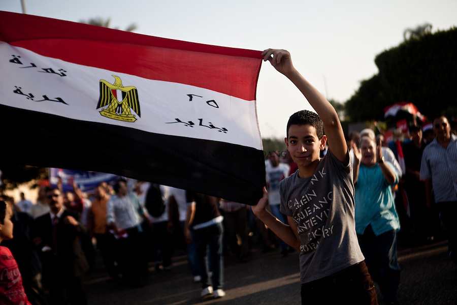 A young boy is carrying an egyptian flag during a march from Nour Mosque to the Presidential Palace in Cairo, Sunday, June 30, 2013. Thousands of people were marching to the Presidential Palace to protest against the Egyptian President Mohammed Morsi and to ask for his removal. Several other mass protest were happening in other big cities of Egypt against his Presidency.<br /> <br /> A jeune garcon porte un drapeua egyptien pendant une marche qui partait de la Mosque Nour au palais presidentielle le dimanche 30 juin 2013.<br /> Des milliers de personnes defilaient au palais presidentiel pour protester contre le president egyptien Mohammed Morsi et pour demander son retrait. Plusieurs autres manifestations de masse se passait dans d'autres grandes villes d'Egypte contre sa presidence.
