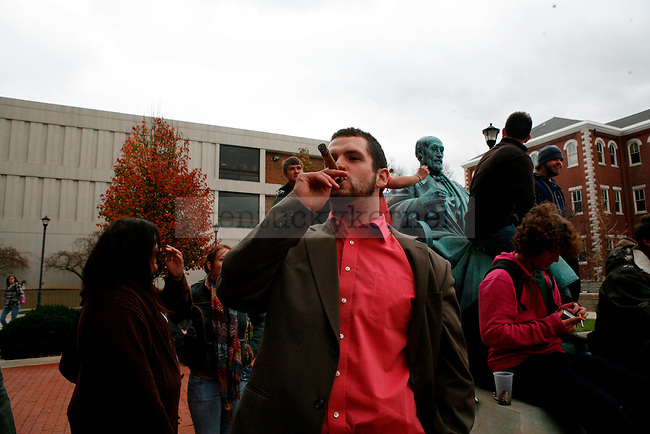 Political science junior Jacob Sims smokes a cigar outside of Patterson Office tower to protest the new tobacco ban on UK's campus on Thursday, Nov. 19, 2009.