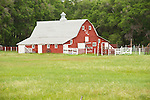 Red barn with cupola ventilator and brand on the end, corral, Sand Hills of Nebraska