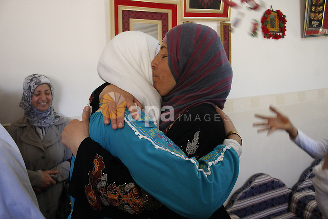 A Palestinian student from the top ten in the general secondary certificate in Palestine, Saja Al-Khadour, 99.5, is greeted by her family in the West Bank city of Hebron on July 22,2010. Photo by Mamoun Wazwaz