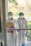 Two public health nurses (Lourdes Goldsmith and Lori Smittle) from the Westchester County Health Department on a home visit to test for COVID-19 in Pleasantville, New York.<br /> <br /> Before entering the home to administer the tests, the nurses stopped on the porch to put on head to toe protective garb.