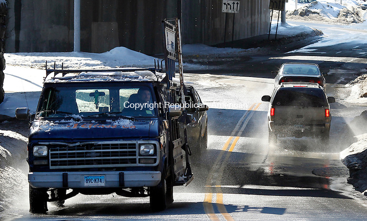 Waterbury, CT- 06, February 2011-020611CM09 Cars drive through large puddles underneath the Metro North overpass on Bank Street in Waterbury Sunday afternoon.  Warm temperatures hit the area melting snow and causing the roadways to fill with water. According to the National Weather Service, today has a slight chance of light rain in the afternoon, otherwise it'll be mostly cloudy, with the highs near 38.   Christopher Massa Republican-American