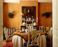 A warm orange glow radiates from the walls of this dining room and is echoed in the runner on the table laid for dinner