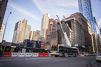 The prestigious Art Students League's French Renaissance style landmark building, right, on West 57th Street in New York is seen covered in scaffolding on Sunday, January 25, 2015. Construction of the foundation for the Extell development which would cantilever 290 feet over the league has begun. The League received $38,1 million in compensation for their air rights. The new skyscraper will be luxury condos and a Nordstrom department store. (© Richard B. Levine)