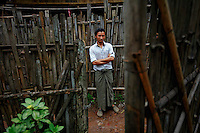 "Wailin Aung, 24 year old ethnic Karen refugee is seen through the gate of a home at the Mae La refugee camp near Mae Sot June 3, 2012. Asked about Aung San Suu Kyi's visit to the camp Wailin Aung said ""I don't understand politics but I don't want to go back to Myanmar. Never."" Myanmar's pro-democracy leader Aung San Suu Kyi visited on Saturday Mae La, the biggest refugee camp along the Thailand-Myanmar border where tens of thousands of her compatriots found shelter after escaping from Myanmar.  REUTERS/Damir Sagolj (THAILAND)"