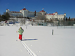 Girl, from back,  in lime green jacket and red ski pants, cross country skis away from viewer  on a sunny field, toward the Mt. Washington hotel.