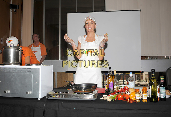 HEATHER MILLS.Heather Mills demonstrates how to to cook fresh vegan meals at the Brighton Eco Veggie Fayre, Hove Town Hall, Hove, England..20th March 2010.half length kitchen cook cooking food hat white apron mouth open plastic gloves .CAP/BEL.©Tom Belcher/Capital Pictures.