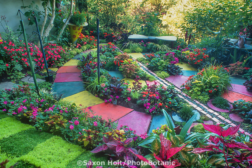 Multicolored cast concrete pavers in whimsical spiral path in backyard garden room with colorful flowering annual bedding plants; design by artist Keeyla Meadows