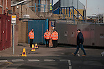 "Stewards on patrol outside Fratton Park stadium before Portsmouth take on local rivals Southampton in a Championship fixture. Around 3000 away fans were taken directly to the game in a fleet of buses in a police operation known as the ""coach bubble"" to avoid the possibility of disorder between rival fans. The match ended in a one-all draw watched by a near capacity crowd of 19,879."