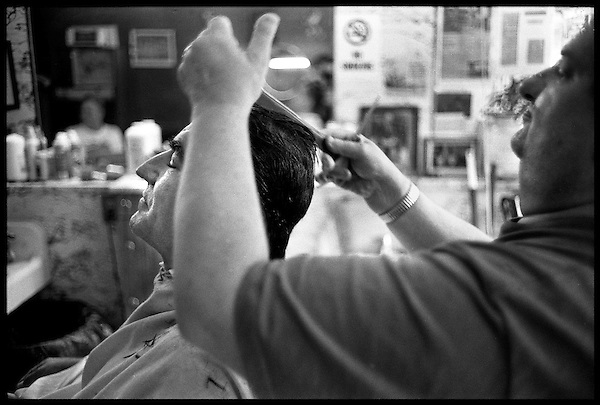 Trust, a customer closes his eyes as Mr. Green works on his hair..