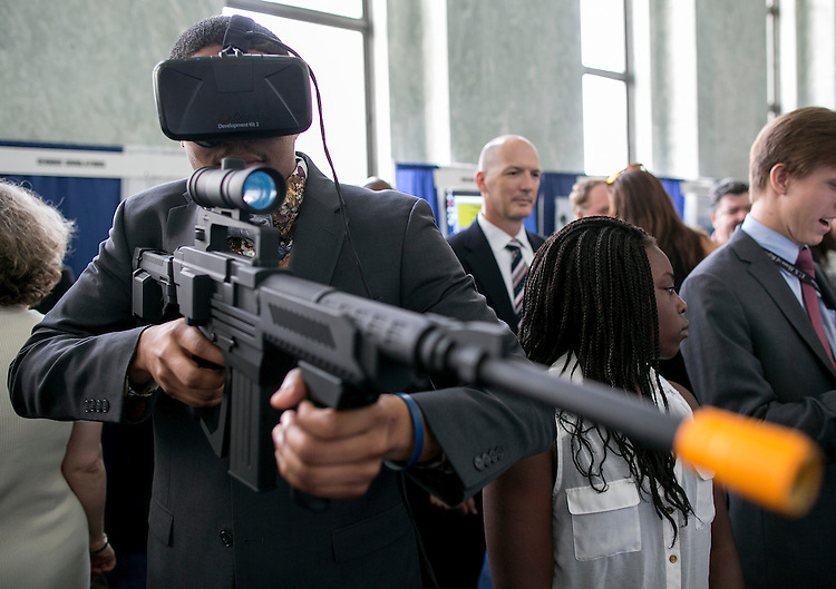 "UNITED STATES - JUNE 9 - Darius Baxter, from the office of Congresswoman Eleanor Holmes Nortan, D-D.C., tries out a virtual reality training video game, made by SAIC Training on Demand, during The National Training and Simulation Association's Capitol Hill Modeling and Simulation Exposition on Capitol Hill in Washington, Thursday, July 9, 2015. The theme of the exposition was ""Modeling and Simulation: Training the Warfighter of the Future While Saving Money,"" and featured several displays with virtual reality and new technology. (Photo By Al Drago/CQ Roll Call)"