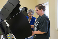 NWA Democrat-Gazette/CHARLIE KAIJO Brenda Taylor (center left) helps Brandy Reeder of Garfield (center right) cast her vote at a voting machine during an election, Friday, July 5, 2019 at the NEBCO Community Building in Garfield. <br /> <br /> The Northeast Benton County Fire Department is holding a special election to increase fire dues.