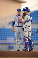 St. Lucie Mets starting pitcher Thomas McIlraith (23) talks with catcher Dan Rizzie (7) on the mound during a game against the Dunedin Blue Jays on April 19, 2017 at Florida Auto Exchange Stadium in Dunedin, Florida.  Dunedin defeated St. Lucie 9-1.  (Mike Janes/Four Seam Images)