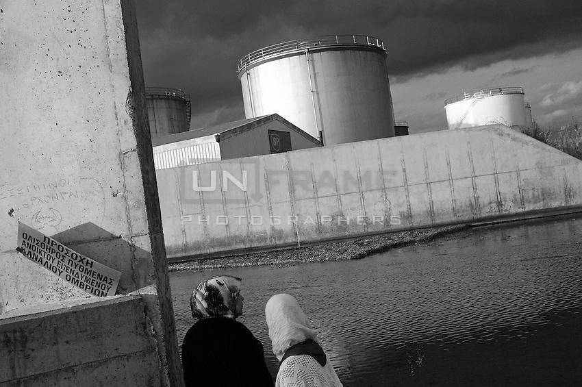 Two women take a stroll near the oil refinery in Larnaca