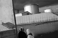 Two women take a stroll near the oil refinery in Larnaca