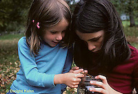 1M17-261z  Children feeding grasshopper to praying mantis nymph - Tenodera aridifolia sinensis