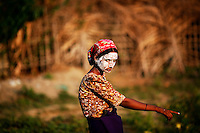 A Rohingya Muslim woman wearing traditional thanaka paste on her face gestures at the camp for people displaced by violence near Sittwe April 26, 2013. Picture taken April 26, 2013.   REUTERS/Damir Sagolj (MYANMAR)