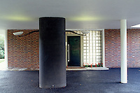 The front door is framed with glass blocks in front of which stands a pillar covered in black mosaic tiles